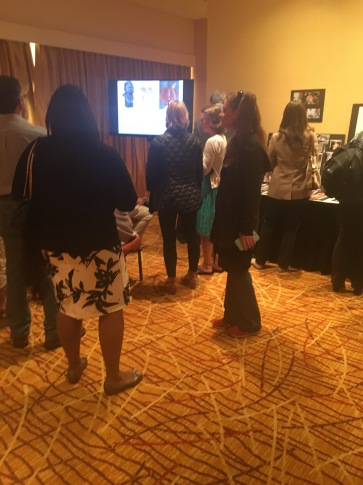 Conference visitors viewing slide show, created by Lauren A. Toomer
